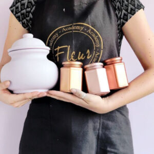 Pots painted with Fleur metallic paints being held by a woman in a black apron